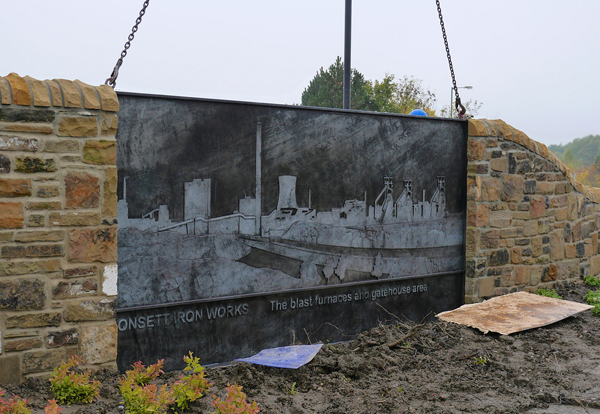 Two steel feature artwork panels are dropped into place at the main vehicular entrance to the new TESCO Extra store in Consett
